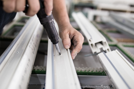 Fabrik für die Herstellung von Fenstern und Türen aus Aluminium und PVC. Arbeiter beim Zusammenbau von PVC-Türen und -Fenstern. Standard-Bild
