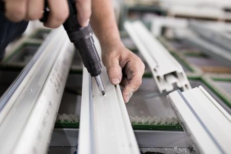 Fabryka do produkcji okien i drzwi z aluminium i PCV. Pracownik fizyczny montujący drzwi i okna PCV. Zdjęcie Seryjne