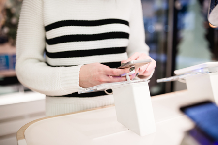 Close up shot of beautiful woman shopping. She standing in mobile phone shop and choosing next model for her. Imagens