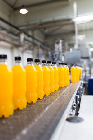 Bottling factory - Orange juice bottling line for processing and bottling juice into bottles. Selective focus. Archivio Fotografico