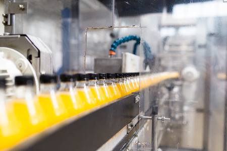 Bottling factory - Orange juice bottling line for processing and bottling juice into bottles. Selective focus. Imagens