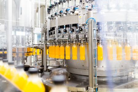Stabilimento di imbottigliamento - Linea di imbottigliamento di succo d'arancia per la lavorazione e l'imbottigliamento del succo in bottiglie. Messa a fuoco selettiva.