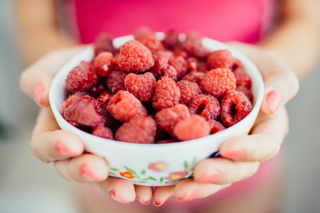 white plate with raspberries in womens hands Stock Photo