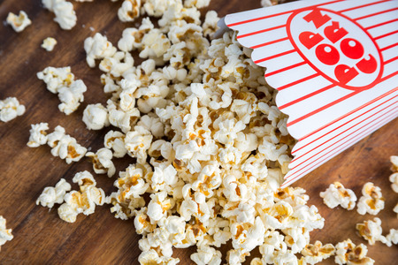 fresh pop corn: Fresh popcorn spilled from container Stock Photo