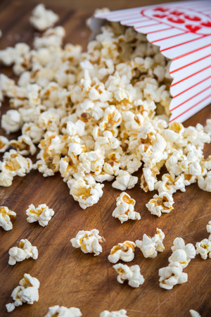 fresh pop corn: Fresh popcorn spilling from container Stock Photo