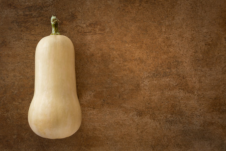 Butternut squash on brown background