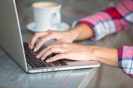 mecanografía: Manos de mujer escribiendo en la computadora portátil