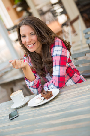 woman eating cake: Cafe woman eating cake and coffee Stock Photo