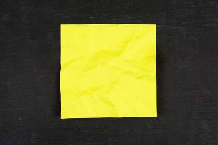scrunched: Yellow sticky note on chalkboard