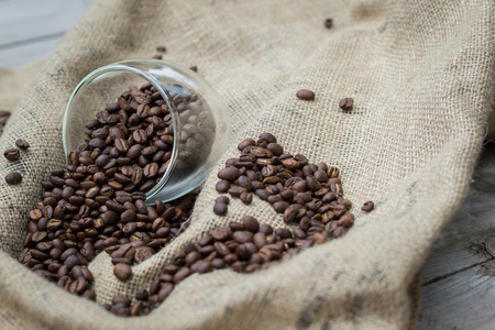 caffeinated: Coffee beans spilling out of glass Stock Photo