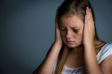 battered woman: Scared and intimidated teenage girl with hands on ears