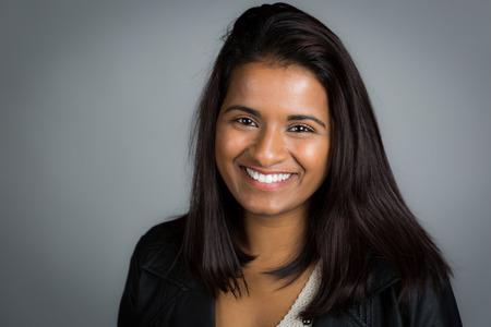 mujeres morenas: Sonriente mujer india en fondo gris Foto de archivo