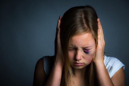 intimidated: Young blonde girl with hands over ears, scared and intimidated Stock Photo