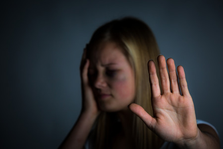 beaten: Young blonde girl with bruised face holds hand up to say stop