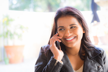woman on cell phone: Indian woman talks on cell phone at cafe Stock Photo