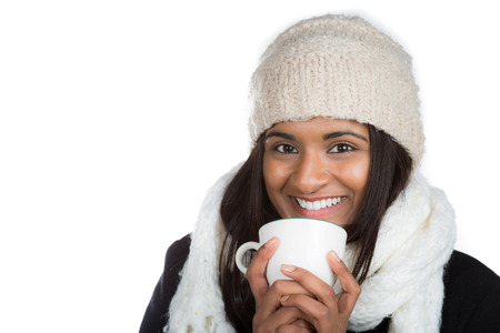 Smiling Indian woman dressed in warm winter clothes and holding coffee mug Stock Photo