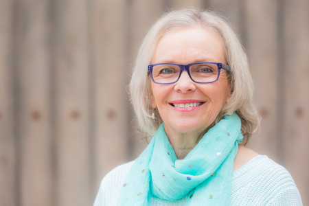 aged: A happy blonde middle aged woman smiling with glasses