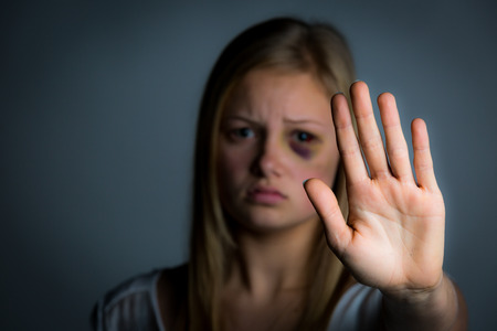 domestic: Abused young girl with hand up to say stop Stock Photo