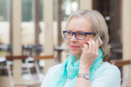 60's: A blonde woman in her 60s listens on her cell phone