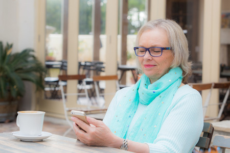 cafe: Middle aged woman sits at cafe texting or operating her smart cell phone