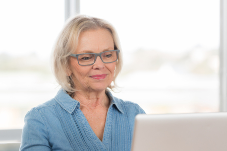 60's: A good looking woman in her 60s sits at a laptop computer