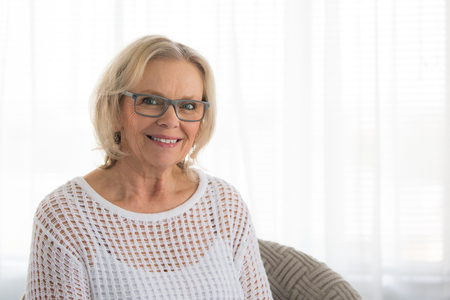 Middle aged blonde woman with glasses smiling while sitting in a chair at home Stock Photo