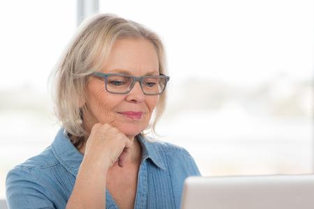 persona mayor: Una anciana se sienta en la computadora portátil Foto de archivo