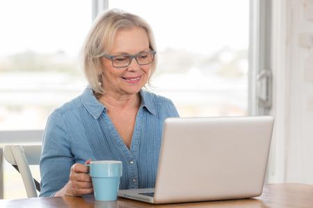 persona feliz: Mujer rubia de mediana edad en vidrios se sienta en el escritorio con el ordenador portátil y el café