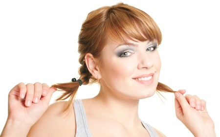 Joyful attractive redhead girl hold for pigtails on white background