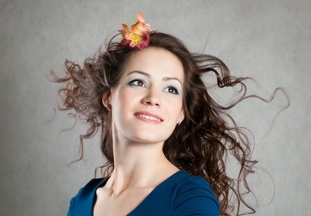 Beautiful young smiling woman with fly-away hair, blowing hair
