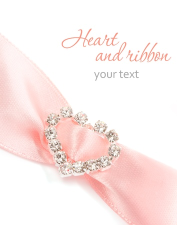 Pink satin ribbon with shining heart on a white background Stock Photo
