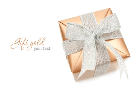 Gold box with silver ribbon on white background. Copyspace