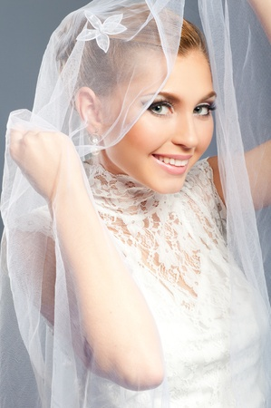 Smiling bride peeks out from under the veil wedding photo