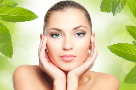 Beautiful woman face on green nature background photo