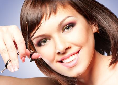 peluquerias: Atractivo sonriente ni�a con unas tijeras, cortar el pelo Foto de archivo