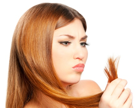 the split: Beautiful woman holding split ends of her hair and frown Stock Photo