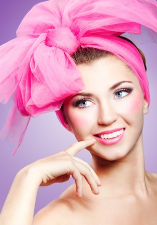 Beautiful smiling girl with pink makeup and bow on head Imagens