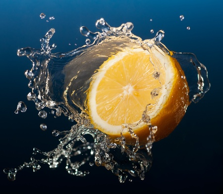 Lemon in water splash on blue background photo