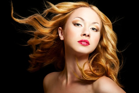Beautiful woman with a flying gold curly hair on a black background photo