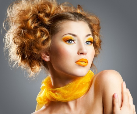 Beautiful woman with bright creative yellow makeup and curly hairstyle
