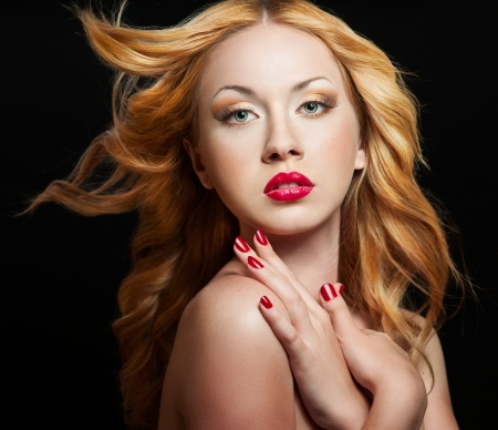 Beautiful woman with bright red lips and manicure and curly hair photo