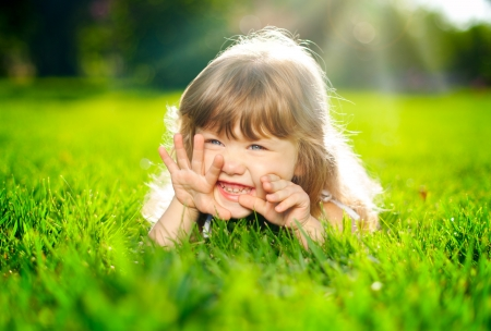 Little smiling girl lying on grass