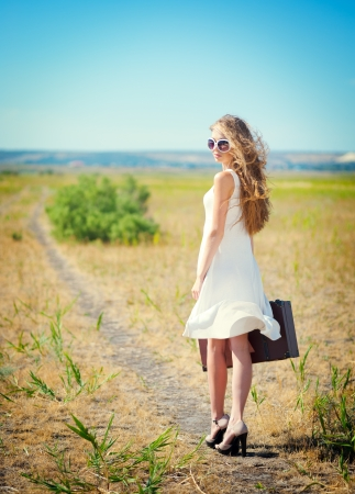 Beautiful Woman holding a suitcase standing on a road Stock Photo - 15045358