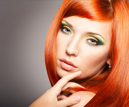 Beautiful Woman with long Red Hair and bright makeup photo