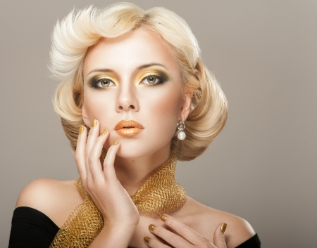 Beautiful woman face with luxury gold makeup Imagens