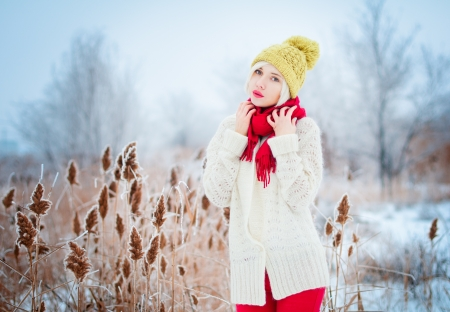 Winter blonde Woman portrait. Beautiful fashion model girl in bright hat and scarf photo