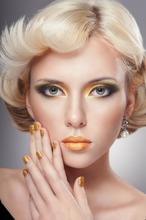 Beautiful woman face with luxury gold makeup Stock fotó