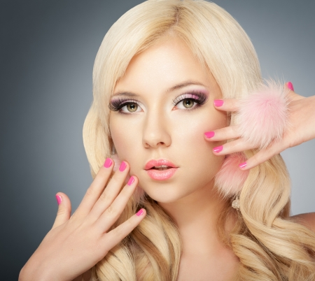 Beautiful blonde girl face with pink makeup, manicure and long eyelashes photo