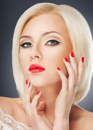 Blonde woman with bright red lips and manicure photo