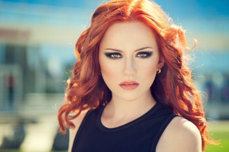 Summer portrait of beautiful woman with red hair and smoky eyes makeup